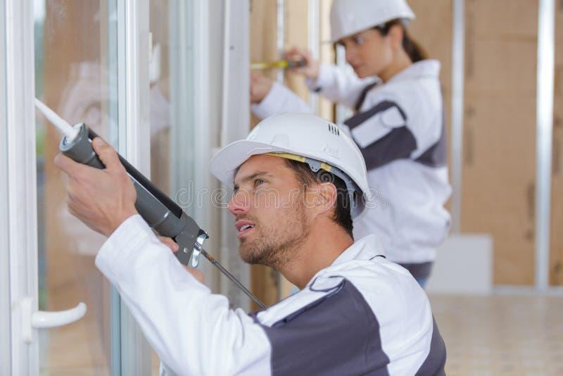 安装窗口的建筑工人在房子 免版税库存照片