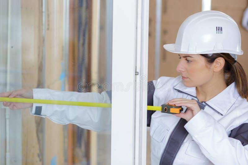 安装窗口i的女性建筑 免版税图库摄影