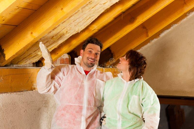 安装绝缘材料屋顶上升暖流的夫妇 免版税库存图片