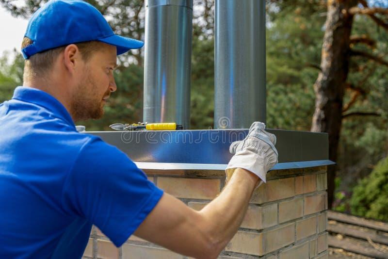 安装罐子盖帽的屋顶的白铁匠在砖烟囱 库存图片