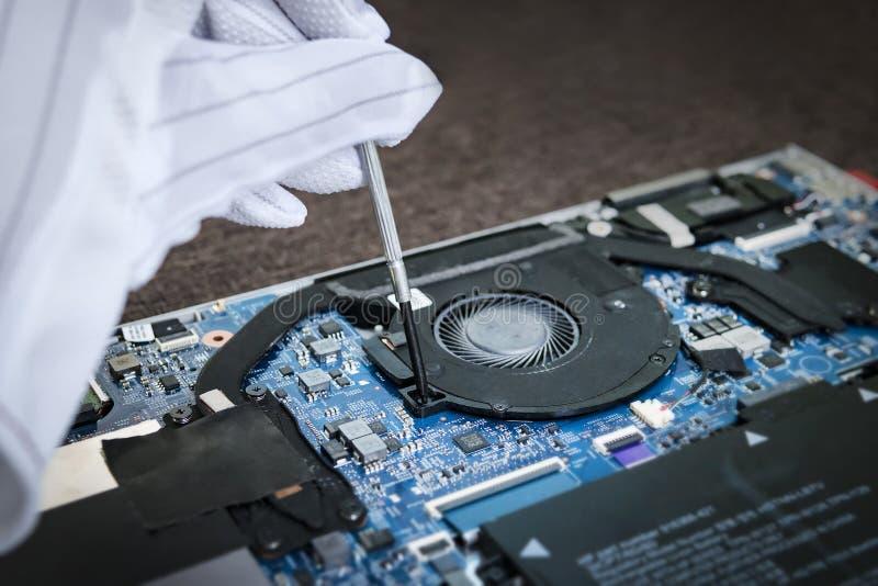 安装膝上型计算机的白色手套的人扇动使用螺丝刀 在现代稀薄的ultrabook的替换致冷机 清洗整修 库存图片