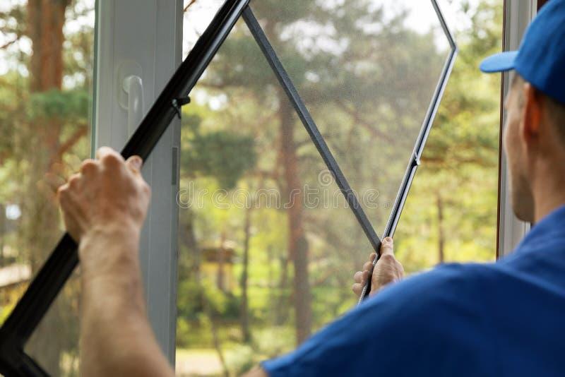 安装蚊帐铁丝网的人在房子窗口 免版税库存图片
