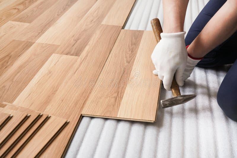 安装被碾压的地板,细节在修理有锤子的人手一个瓦片,在白色泡沫基极层 库存图片