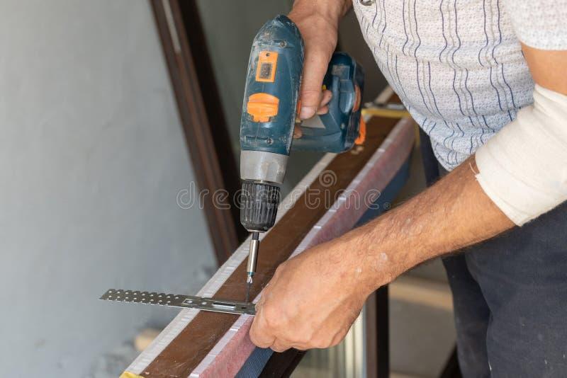 安装金属船锚板材的人在窗架 库存图片