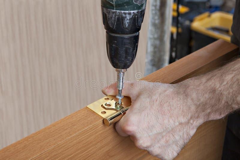 安装门折页,拧紧螺丝的木匠使用screwdri 免版税图库摄影