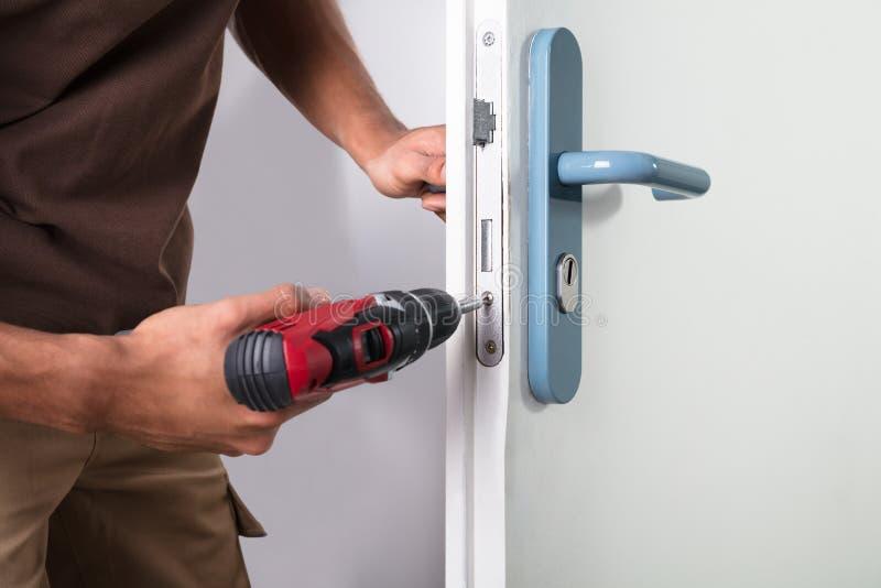 安装门锁的木匠 图库摄影