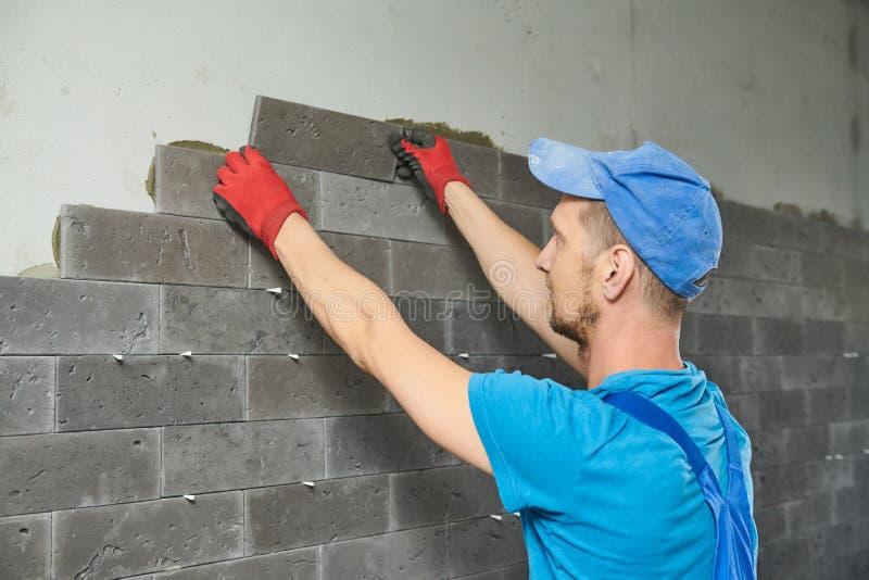 安装陶瓷砖盘区的铺磁砖工在大厅 免版税库存图片