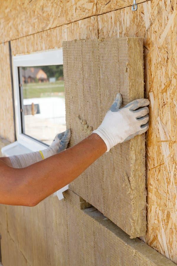 安装绝缘材料的建造者工作者在墙壁 免版税库存图片