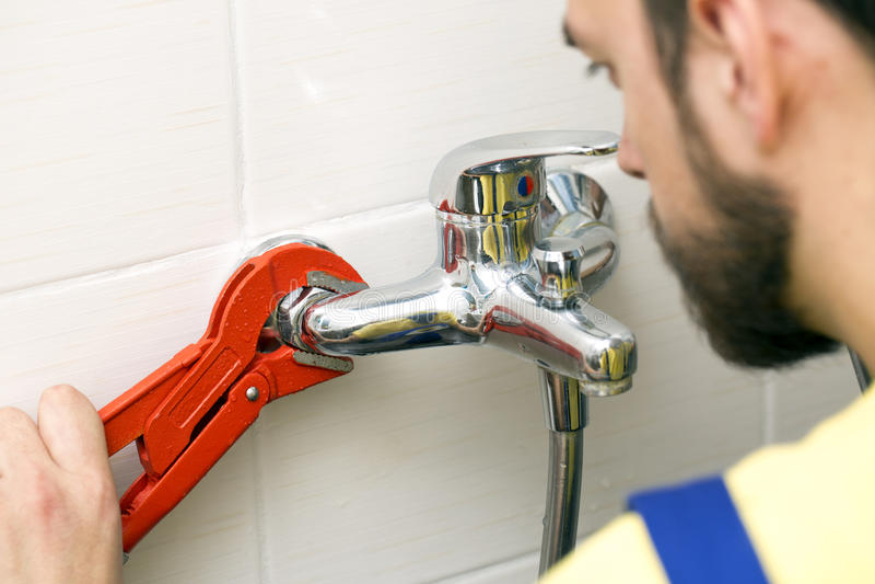 安装水龙头的水管工在卫生间 库存照片