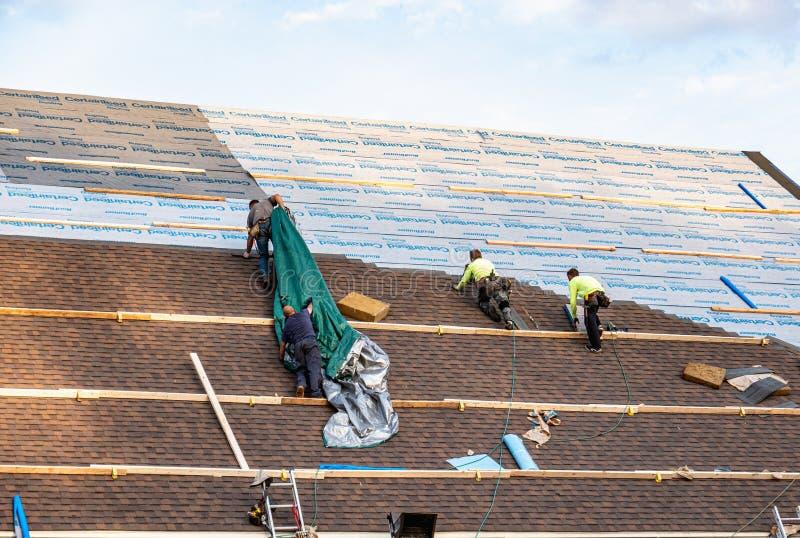 安装CertainTeed屋顶产品的盖屋顶的人 库存照片