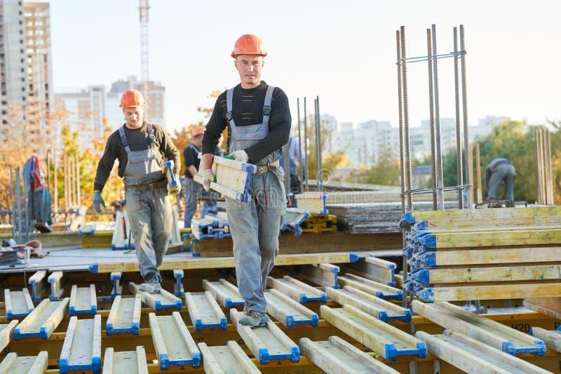 安装wormwork的大厦区域的建筑工人 免版税库存照片