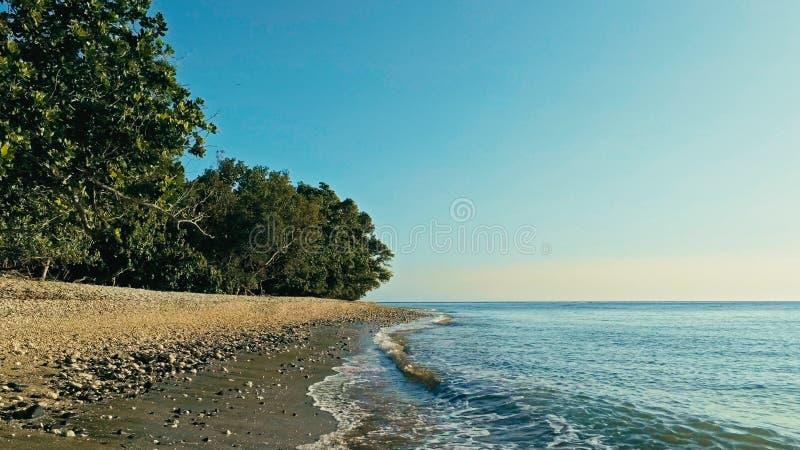 安静和惊人的美丽的暗藏的遥远的海洋海岸的放松的空中寄生虫图象在日落的与一个不尽的沙滩 免版税图库摄影