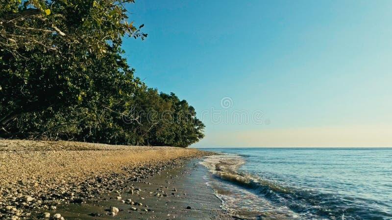 安静和惊人的美丽的暗藏的遥远的海洋海岸的放松的空中寄生虫图象在日落的与一个不尽的沙滩 免版税库存照片