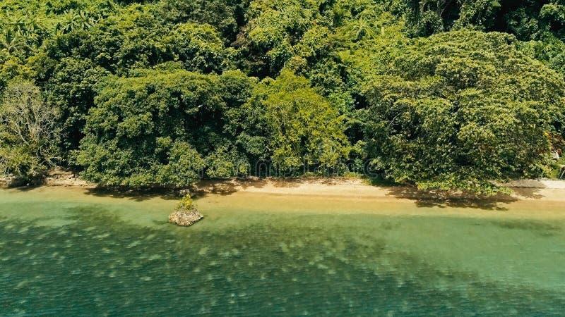 安静和惊人的美丽的暗藏的遥远的海洋海岸的放松的空中寄生虫图象在日落的与一个不尽的沙滩 免版税库存图片