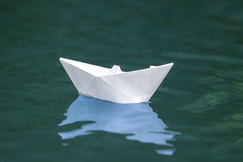 安静地漂浮简单的小白色origami纸的小船特写镜头  免版税库存图片
