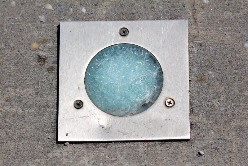完全地在地板光反射器的残破的玻璃登上了与金属框架和三个螺丝在具体平台 免版税库存图片