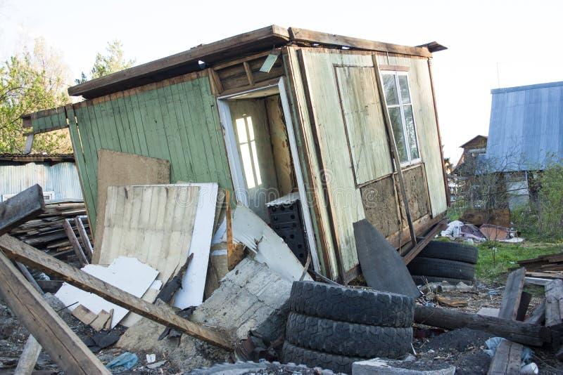 完全地被破坏的房子 在另外垃圾附近,轮胎,板 库存照片
