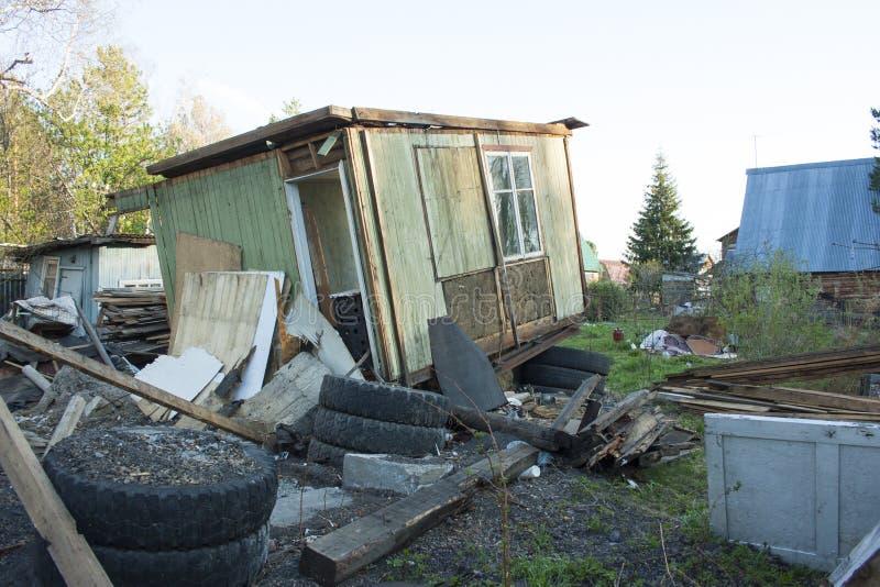 完全地被破坏的木房子 在另外垃圾附近,轮胎,板 免版税库存照片
