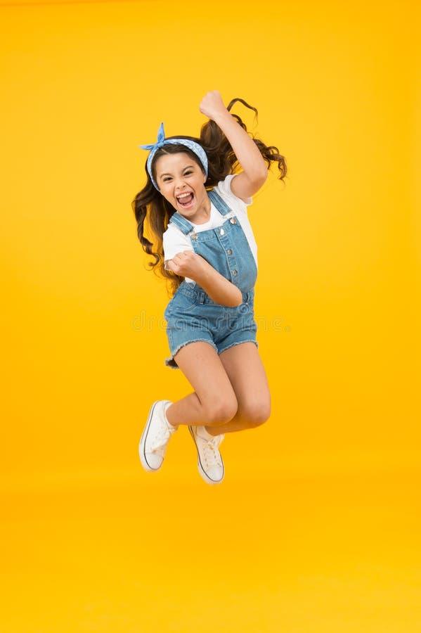 完全快乐 内部能量 感觉自由 暑假 快乐的跳跃 小女孩跳黄背景 享受 免版税库存照片
