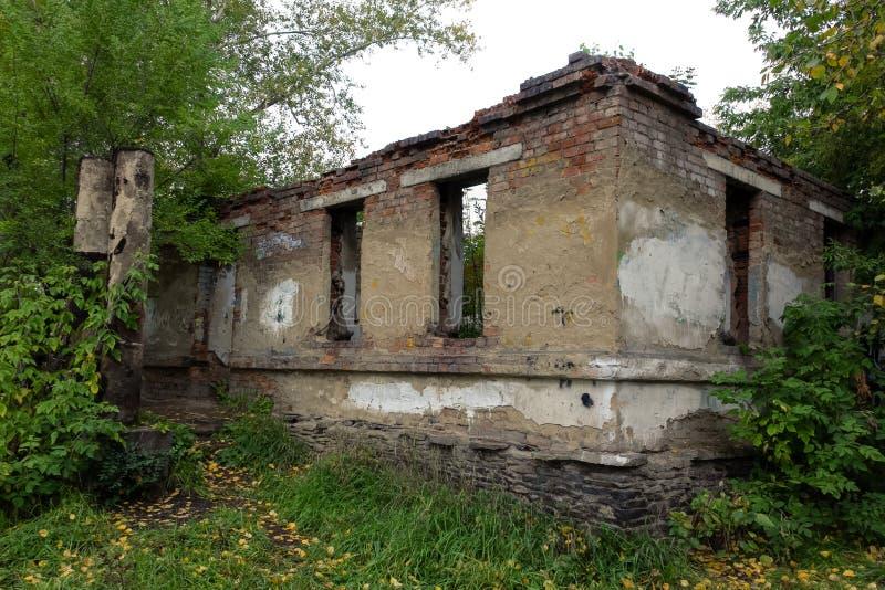 完全荒芜的被破坏的砖房子在秋天树中 库存图片