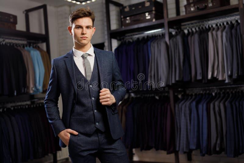 完善对最后细节 现代生意人 塑造一个英俊的年轻人的射击典雅的经典衣服的 人` s 库存图片