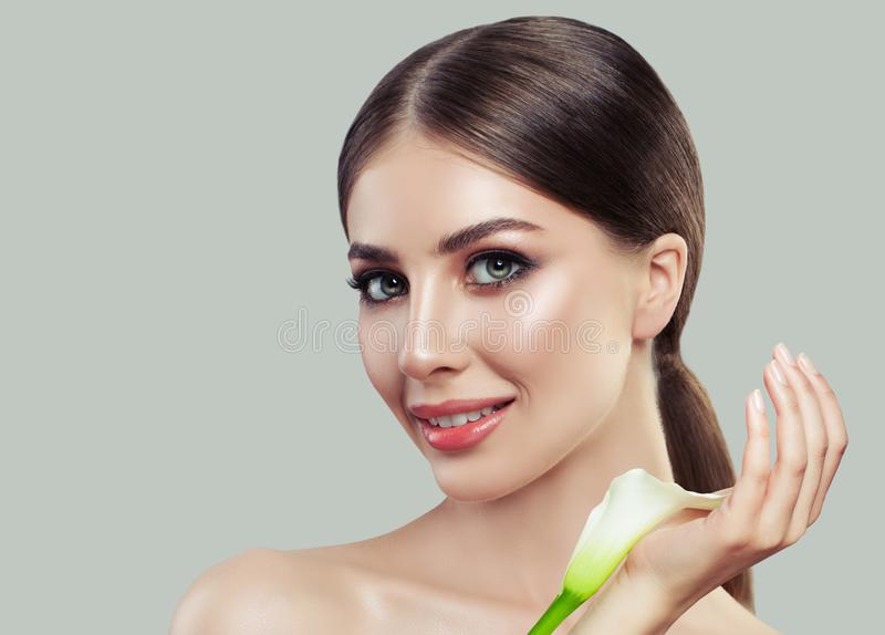 完善有健康皮肤和白色水芋属花的少妇 免版税库存图片