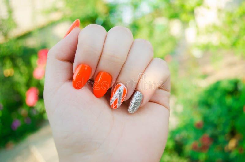 完善的修指甲和自然钉子 有吸引力的现代钉子艺术设计 橙色秋天设计 长的穿着考究的钉子 免版税库存照片