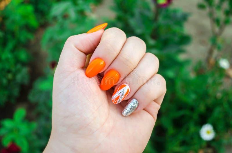完善的修指甲和自然钉子 有吸引力的现代钉子艺术设计 橙色秋天设计 长的穿着考究的钉子 库存照片