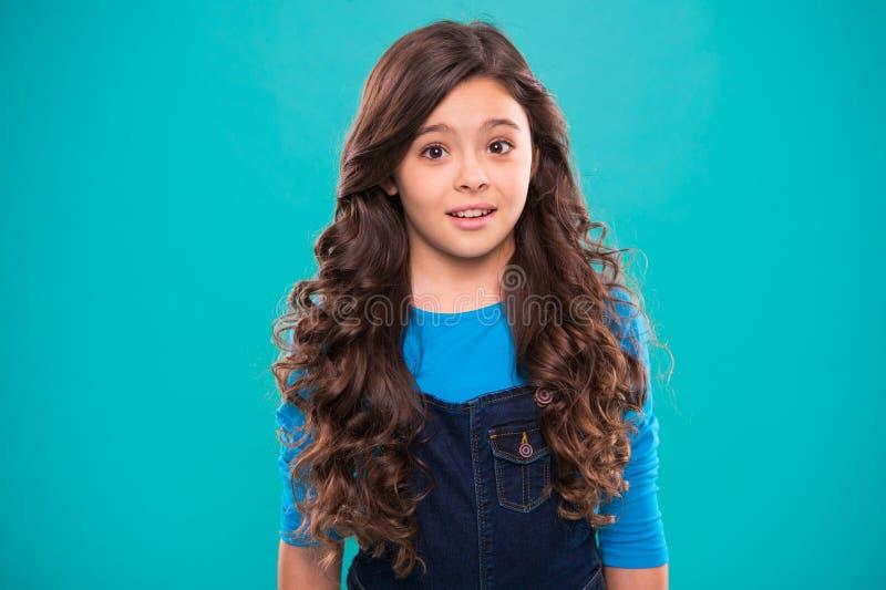 完善的卷曲的头发 教的健康护发习性 孩子女孩长的健康发光的头发 孩子愉快的逗人喜爱的面孔与 免版税库存照片