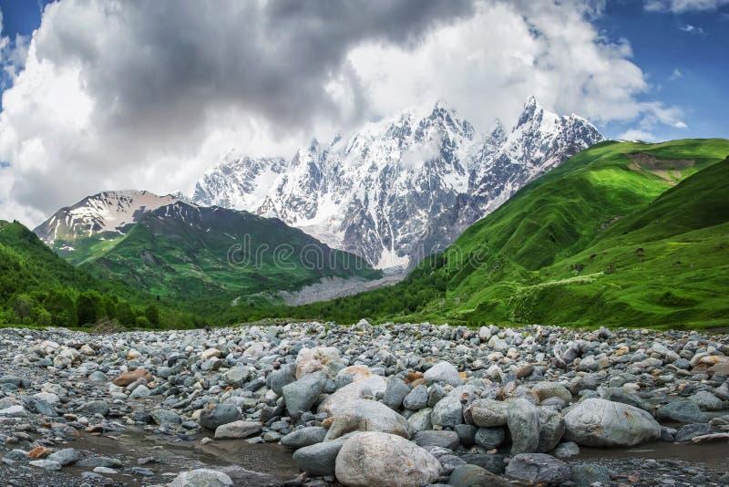完善的山风景在乔治亚, Svaneti 青山、多雪的岩石登上和石头在河岸反对天空与云彩 免版税库存照片