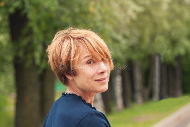 完善的成熟秀丽 美丽的有时髦层状突然移动理发的红头发人老妇人在公园 免版税库存照片