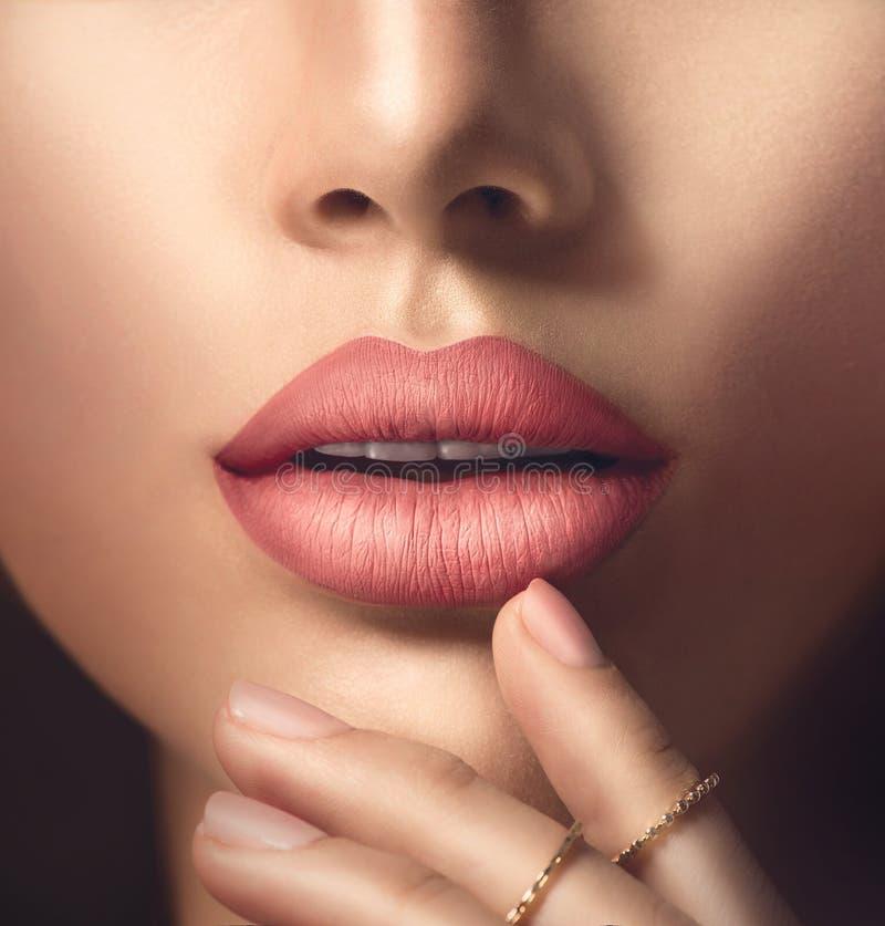 完善的有米黄表面无光泽的唇膏的妇女的肉欲的嘴唇 库存照片