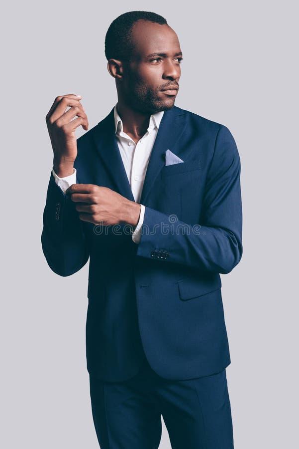 完善的样式 看起来充分的衣服的英俊的年轻非洲人调整他的袖子和去,当站立反对灰色backgrou时 库存图片