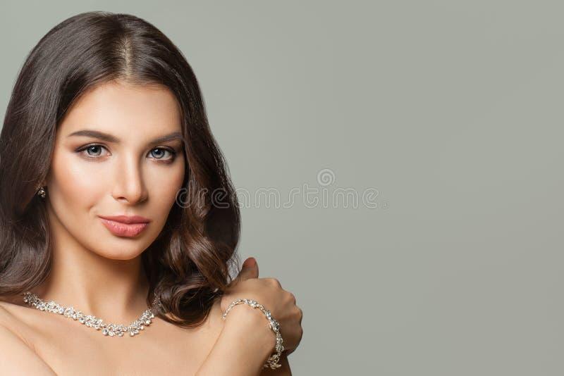 完善的深色的妇女面孔 有构成、长发和金刚石首饰的女孩 免版税图库摄影