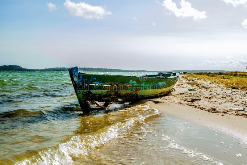 完善的热带天堂海滩和老小船 免版税库存照片