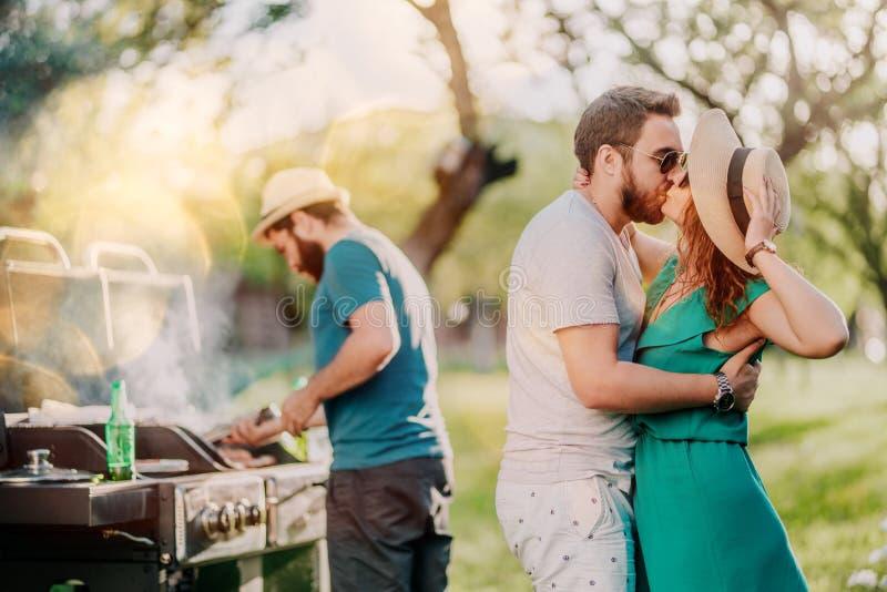 完善的白种人夫妇亲吻在烤肉聚会的,有美好时光和烹调在背景的朋友画象  免版税库存图片