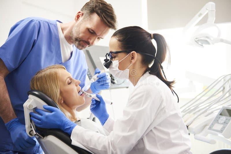 完成他们的在牙医的诊所的牙医和她的助理工作 免版税图库摄影