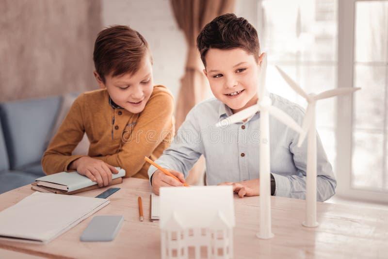 完成他们的家庭任务的两位逗人喜爱的宜人的男小学生 免版税库存照片