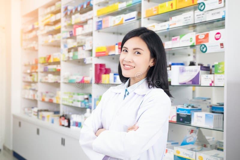 完成他的在药房的美丽的微笑的年轻女人药剂师工作 免版税图库摄影