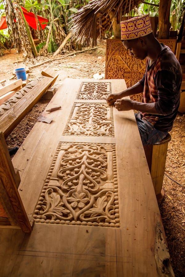 完成他的工作的非洲人做一个雕刻师门 免版税图库摄影