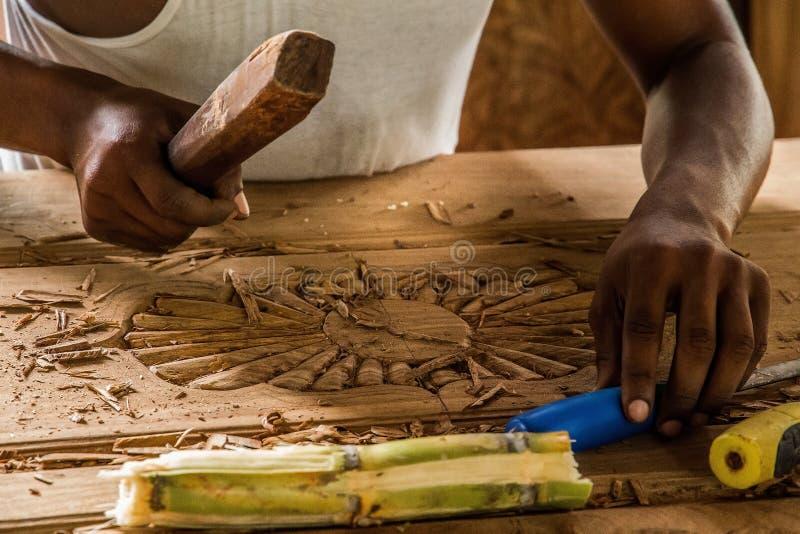 完成他的工作的非洲人做一个雕刻师门 免版税库存图片