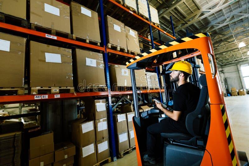 完成后勤学与铲车装载者一起使用的仓库工作者 库存照片
