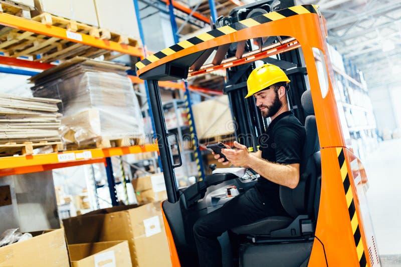 完成后勤学与铲车装载者一起使用的仓库工作者 免版税库存图片