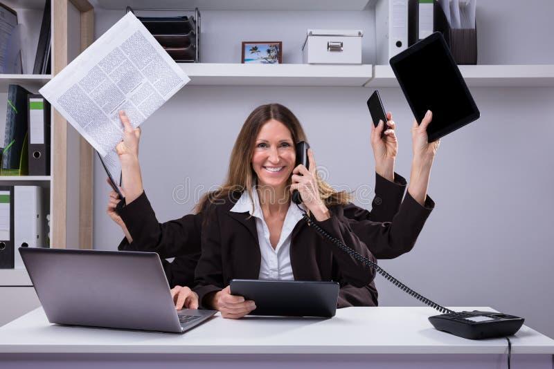 完成多任务工作的女实业家在办公室 免版税库存图片