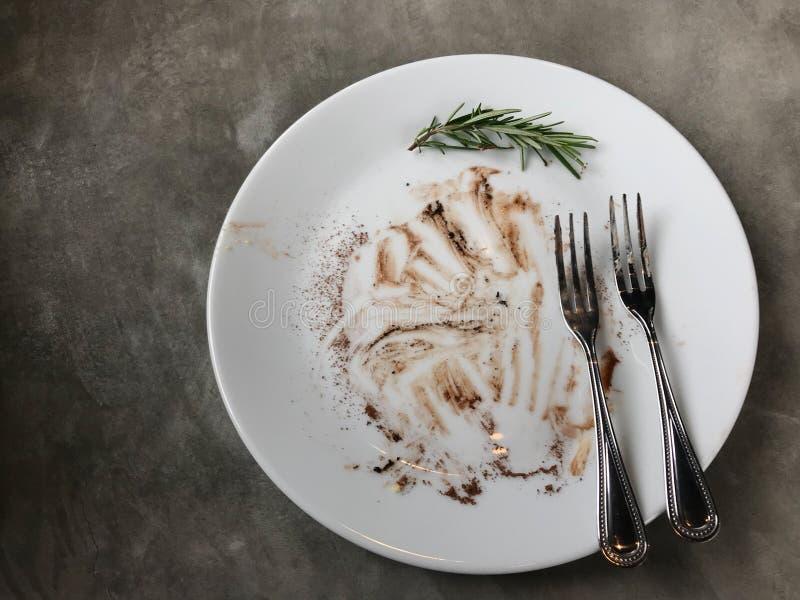 完成的果仁巧克力蛋糕用巧克力弄脏了和叉子和迷迭香在白色盘 库存照片