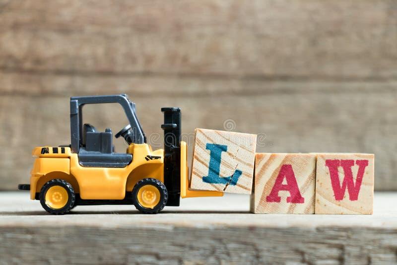 完成词法律的玩具黄色铲车举行信件块L 图库摄影