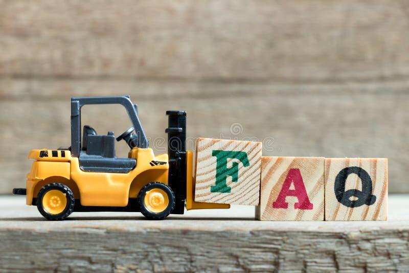 完成词的玩具黄色铲车举行信件块F常见问题解答 免版税库存照片