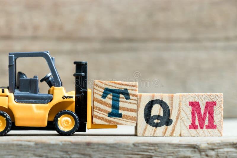 完成词的玩具黄色铲车举行信件块T TQM& x28;总质量management& x29的简称; 免版税库存照片