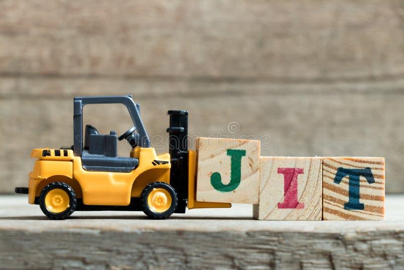完成词JIT简称的玩具黄色铲车举行信件块J及时 免版税库存照片