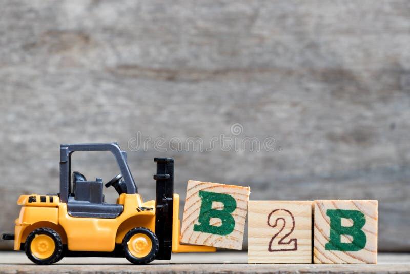 完成B2B的黄色塑料铲车举行信件B 免版税库存图片